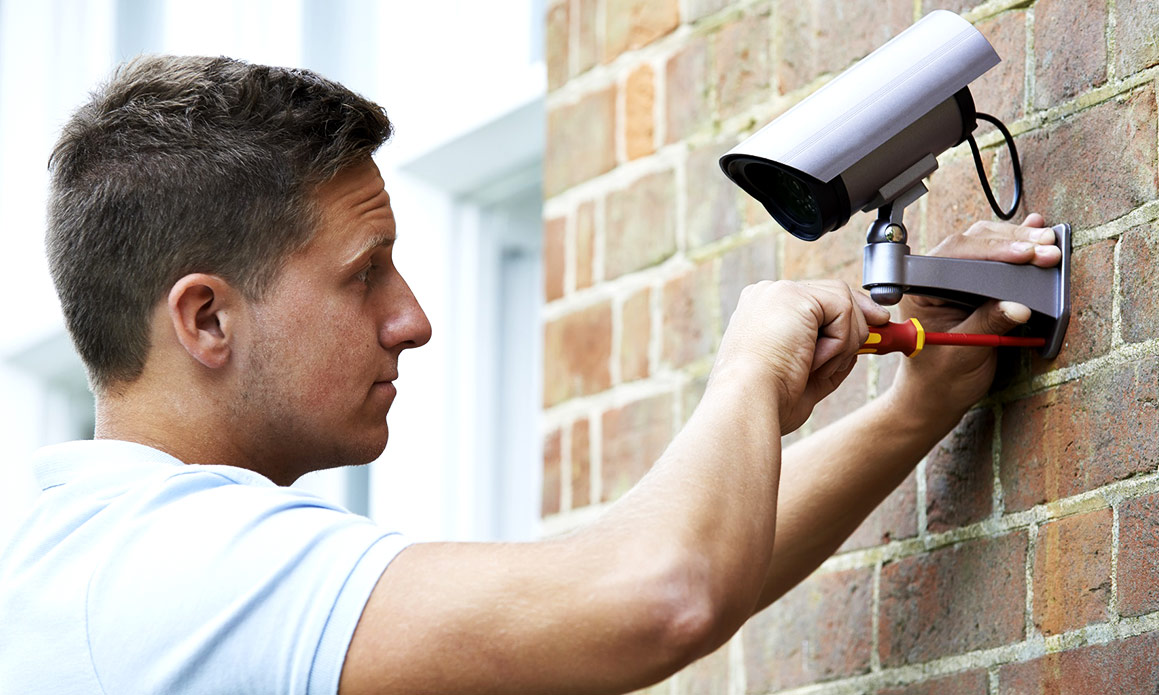 Man installing a security camera on a brick wall