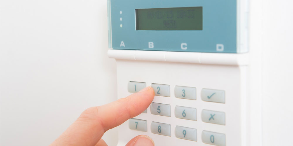 A person deactivating their alarm system by entering their pin code